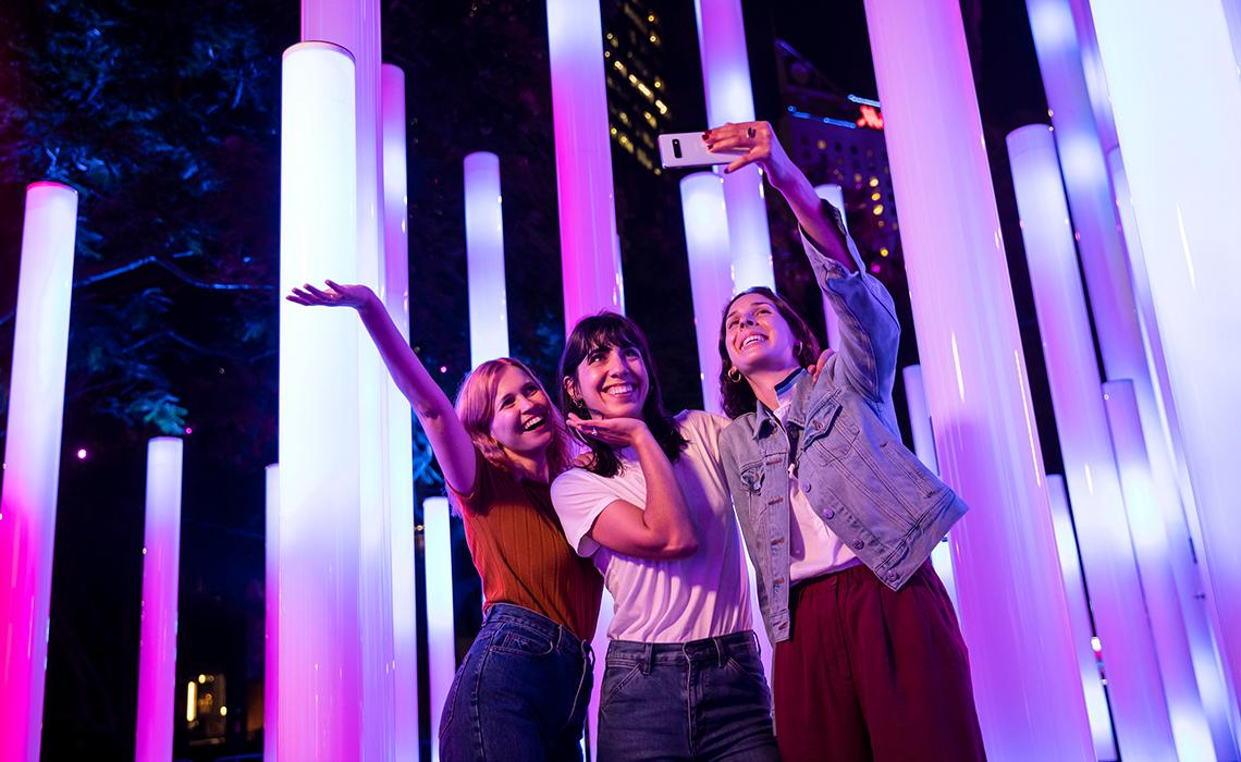 Friends enjoying the Triangulum light installation in East Circular Quay during Vivid Sydney 2019